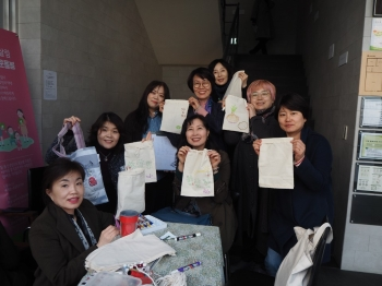 Members of Seoul Hansalim hold the cotton pouches they made. Photo provided by Seoul Hansalim