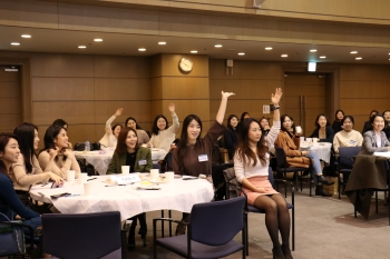 Ewha Voice alumnae raising their hands to answer quizzes about Ewha Voice during homecoming ceremony. Photo by Heo Sol.