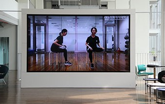 School's Fitness Center provides a guideline video on indoor workoutsfor students at ECC Nae:il Lounge. Photo by Heo Sol.