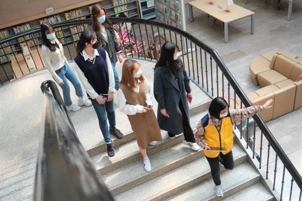 Students are walking down the stairs of the Ewha Centennial Library during their lunch tour.