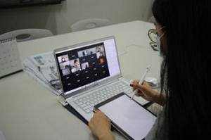 A student takes an online class Zoom class at a table in ECC.