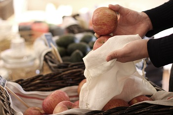 A customer is placing an apple into a pouch instead of using a plastic bag.Photo provided by The Picker.