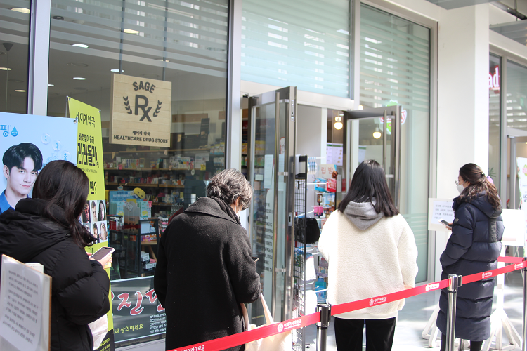 Students waiting to buy masks at ECC pharmacy to fight the novel coronavirus.Even before the semester begins, people are lining up in front of the ECC pharmacy to get masks accordingto the mask rationing system announced by the government.Photo by Ko Yu-seon.