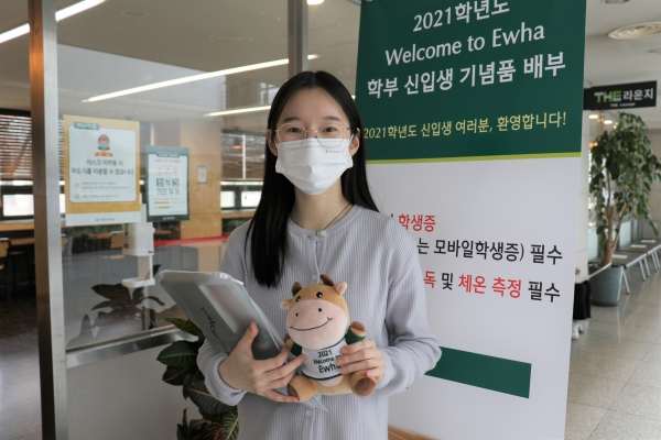 "This is Hanhee Cho, a freshman in Climate and Energy Systems Engineering. Although new students are enrolled at Ewha, they do not have many chances to visit the campus. Cho is holding ""welcome goods,"" which are distributed to freshmen to welcome them to Ewha. Photo by Heo Sol."